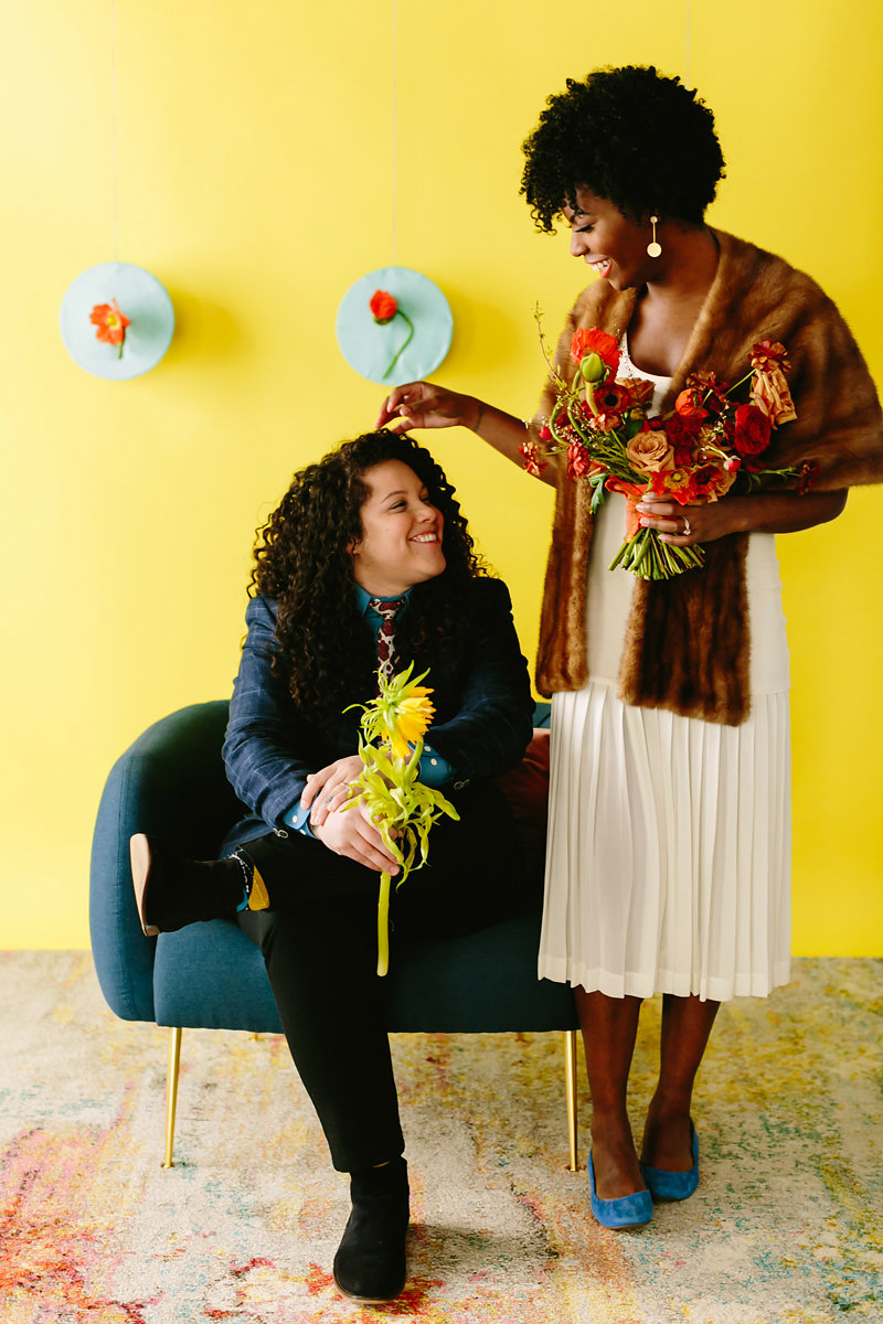 wes anderson inspired wedding brooklyn new york couple against yellow background, one sitting in chair
