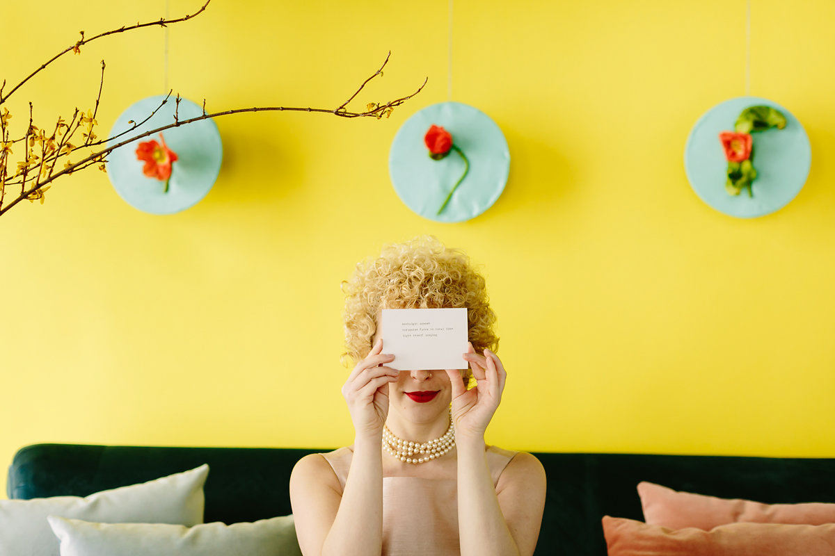 wes anderson inspired wedding brooklyn new york writer holding poem card over her eyes
