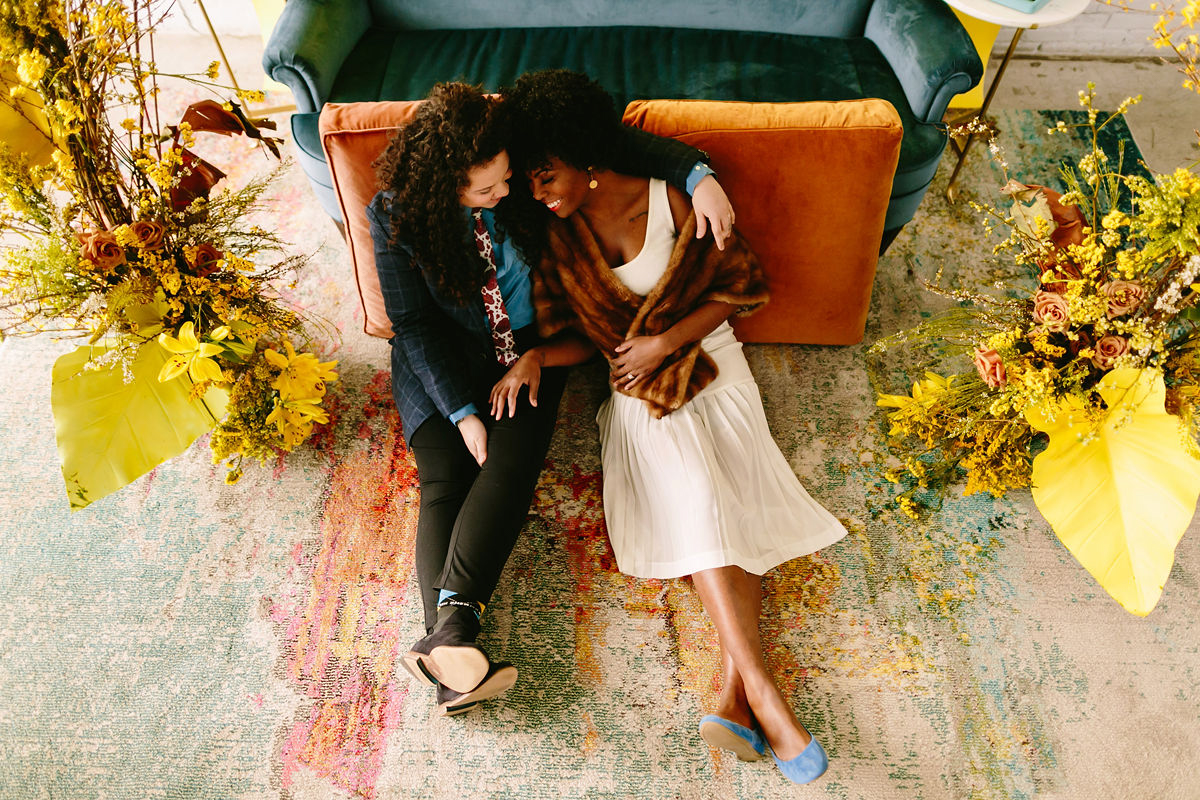 wes anderson inspired wedding brooklyn new york couple sitting on floor against couch with flowers on either side