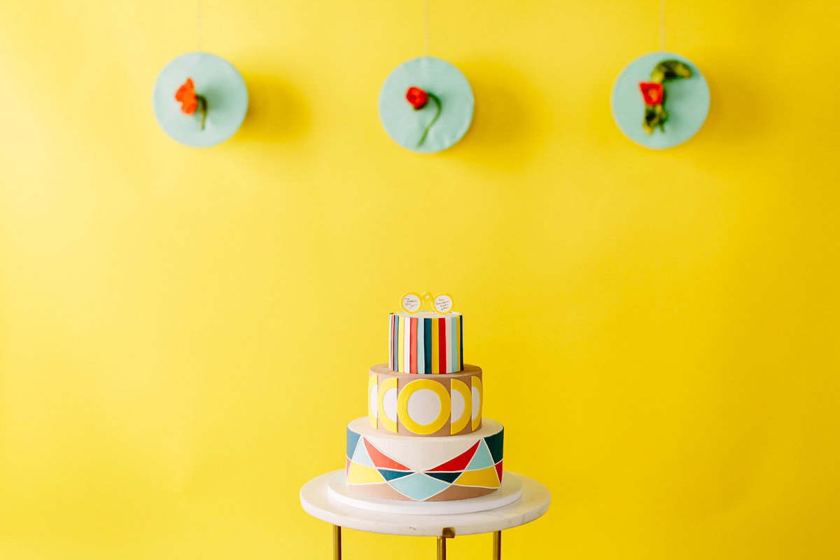 wes anderson inspired wedding brooklyn new york cake against yellow wall with three floral art pieces