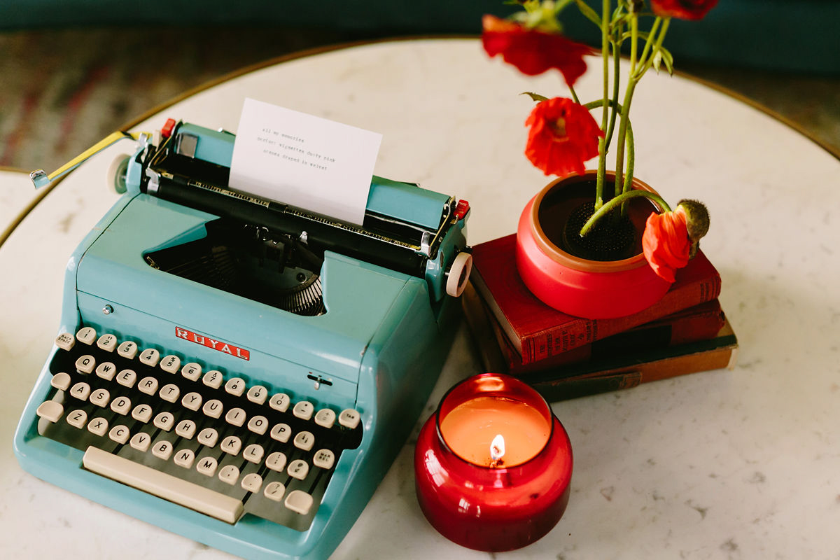 wes anderson inspired wedding brooklyn new york typewriter on table with candle, stack of books, and pot of flowers