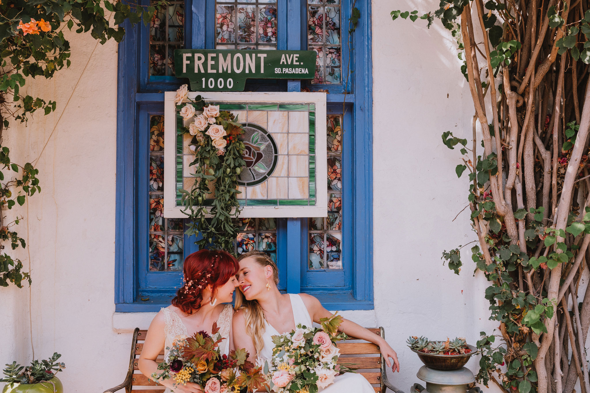 two brides lean in for kiss in front of stained glass window at wedding reception by Rebecca y Las Otras Photography