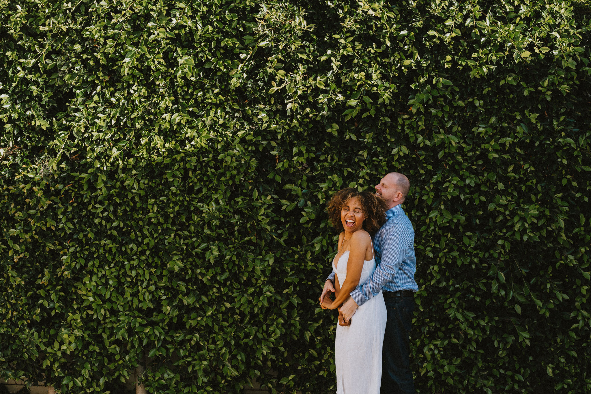 newlywed couple embracing in front of green wall at their wedding by los angeles photographer Rebecca y los otras