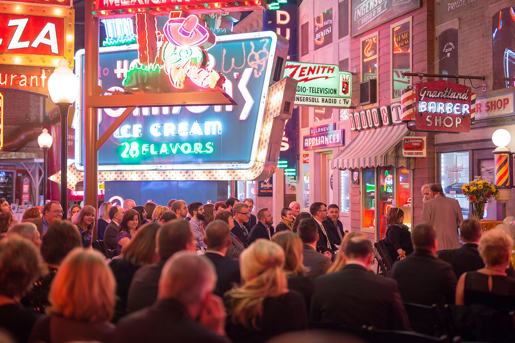wedding guests amid the neon signs at dustin and megan's wedding at the American Sign Museum in Cincinnati