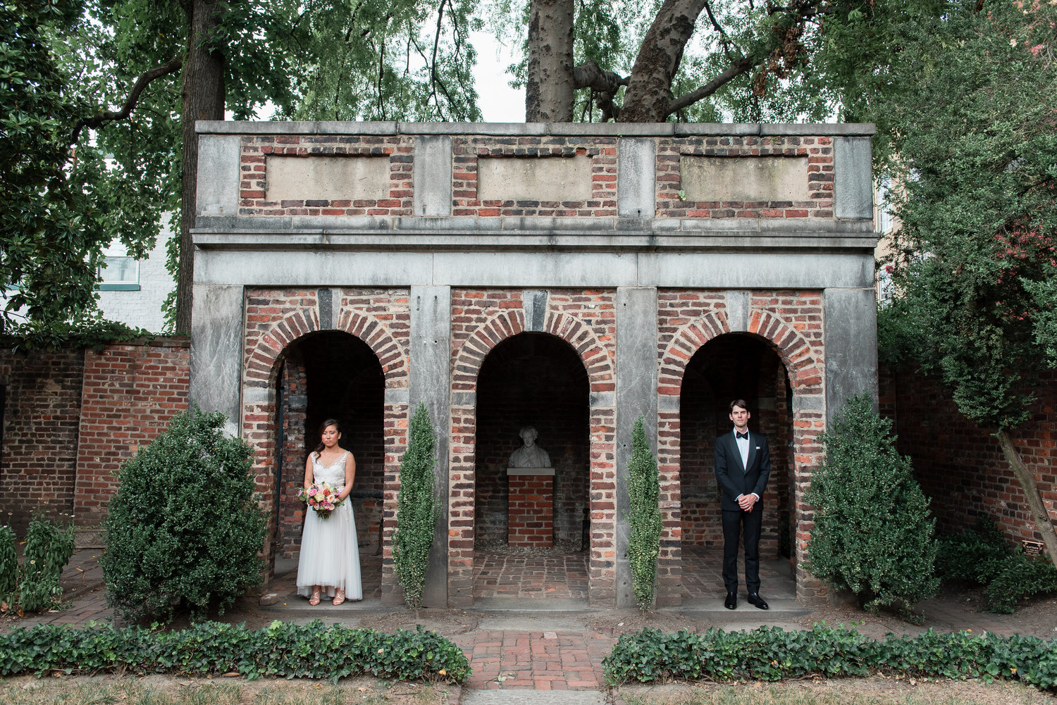 Ben and Christina at wedding standing in archway in garden at Poe Museum in Richmond Virginia
