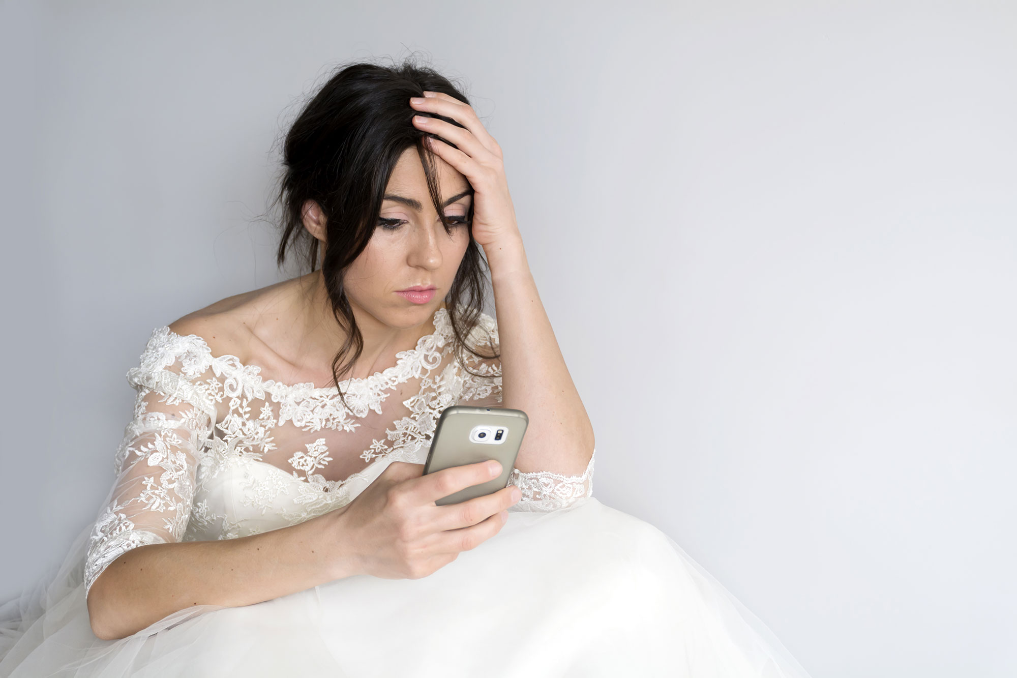 bride in a wedding dress stressed out and looking at her phone
