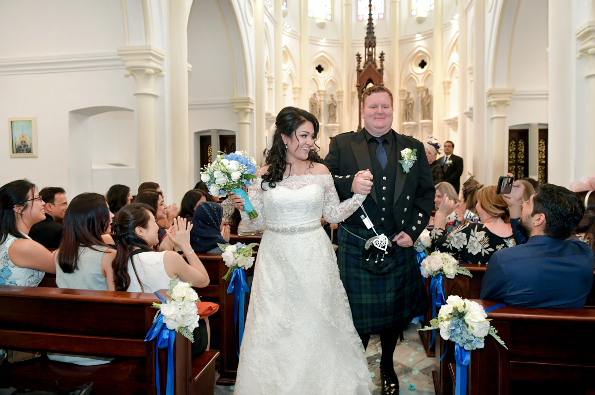 mita in a western wedding dress and james in a scottish kilt walking down the aisle at their western wedding ceremony
