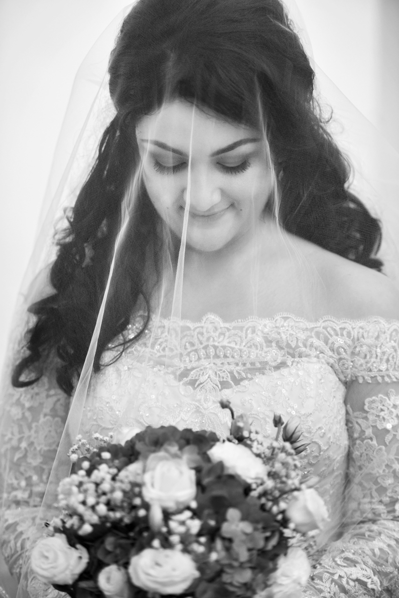 Mita in her western wedding dress and veil holding a bouquet