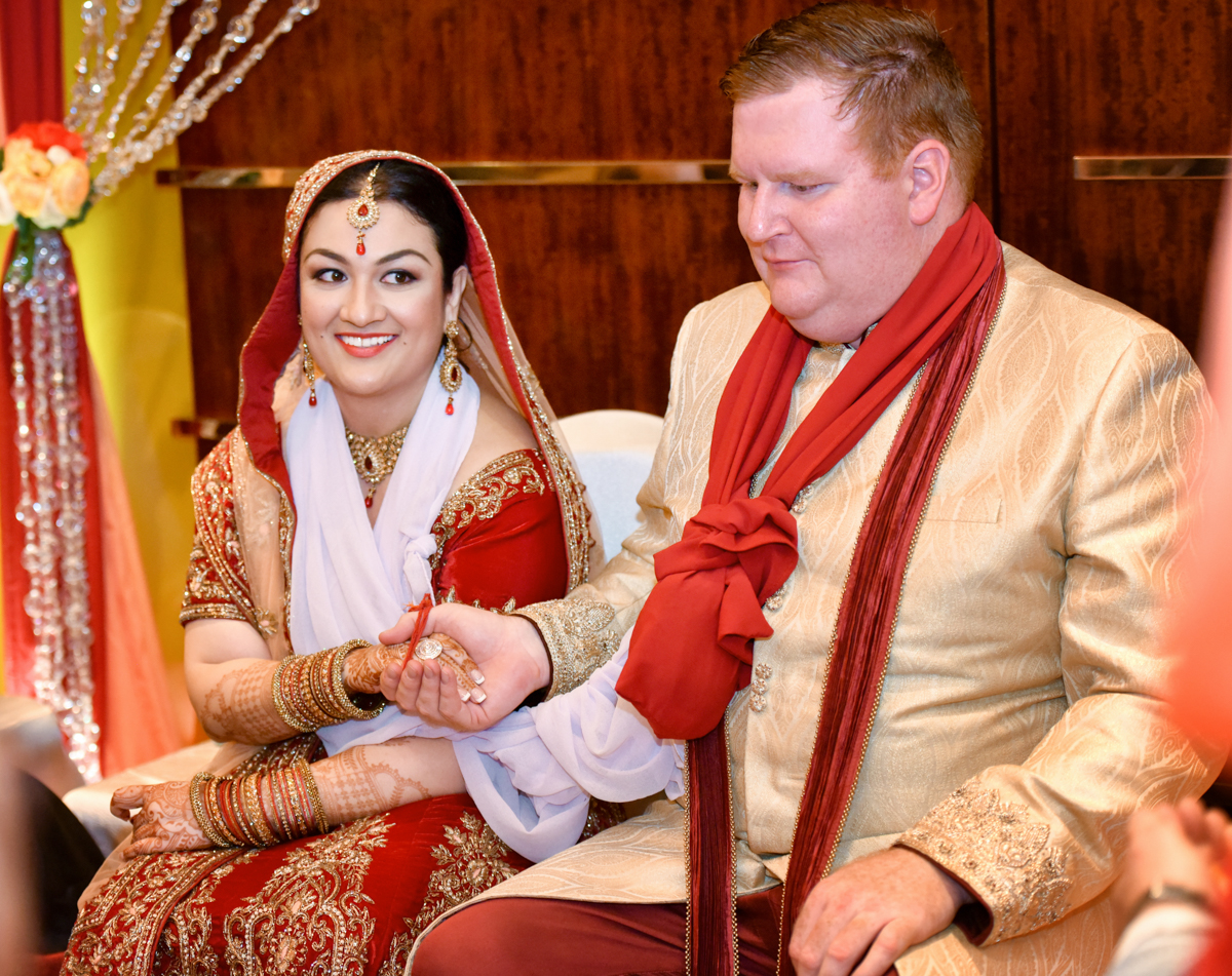 Mita and James holding hands as part of their Indian wedding ceremony in hong kong