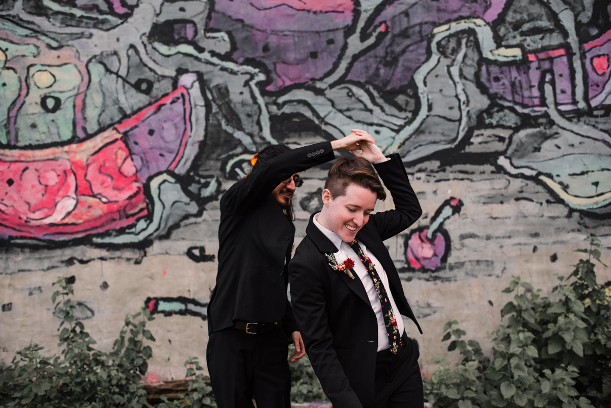 intimate wedding richmond virginia stephan twirling erin in front of wall mural