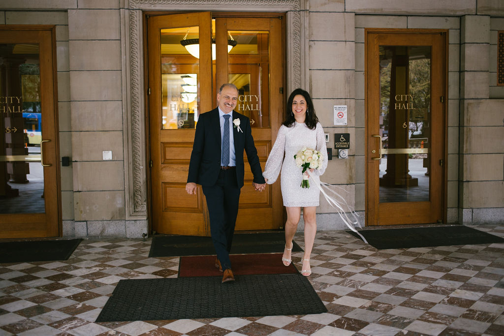 portland rainy elopement maddie maschger photography couple holding hands leaving city hall