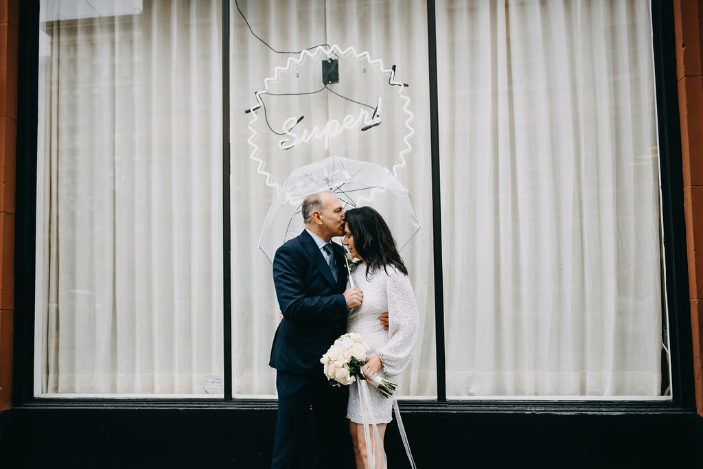 portland rainy elopement maddie maschger photography moreno kissing linda's forehead outside window with neon sign