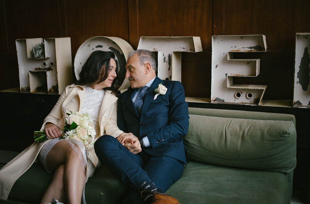 "portland rainy elopement maddie maschger photography couple on couch in front of metal letters reading ""hotel"""