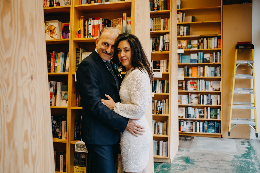 portland rainy elopement maddie maschger photography embrace among stacks of powell's bookstore