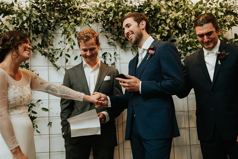 couple holding hands during their wedding ceremony with groomsman crying nearby in Richmond Virginia Carly Romeo & Co