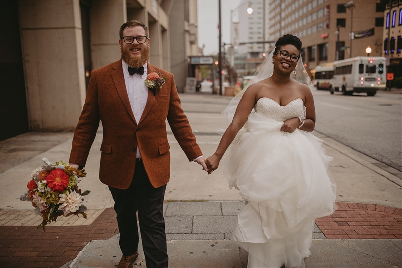 newlywed couple walking down the sidewalk in the city holding hands and smiling Richmond Virginia Carly Romeo & Co