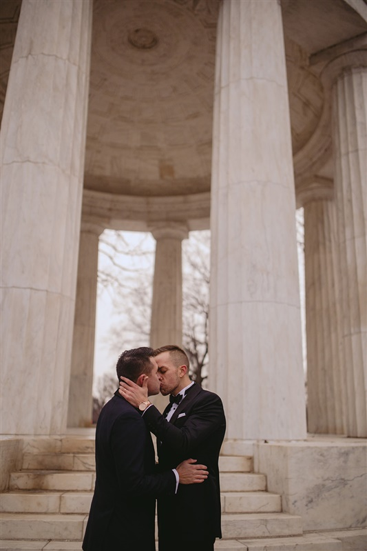 two grooms sharing a kiss at the Jefferson Memorial in Washington DC Carly Romeo & Co