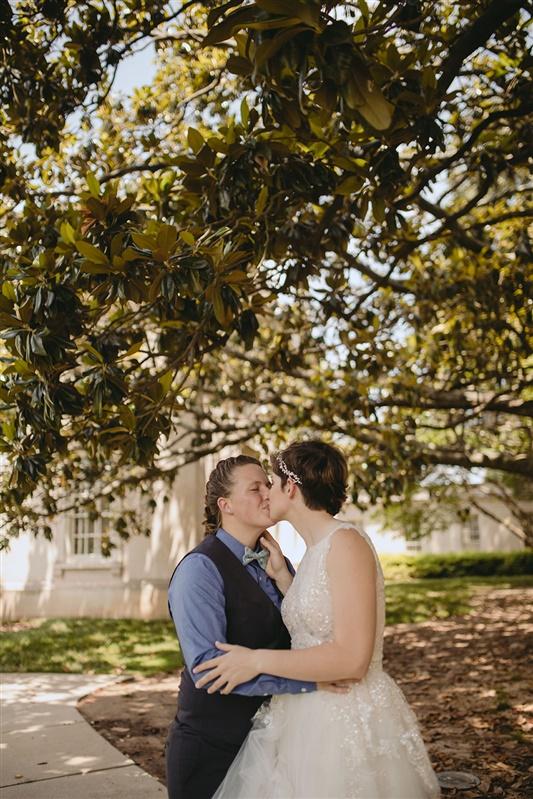 newlywed couple share a kiss under a tree richmond virginia Carly Romeo & Co