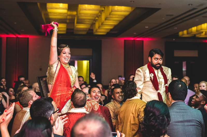 Indian newlywed couple being lifted in chairs by wedding guests at their reception in Richmond Virginia Carly Romeo & Co.