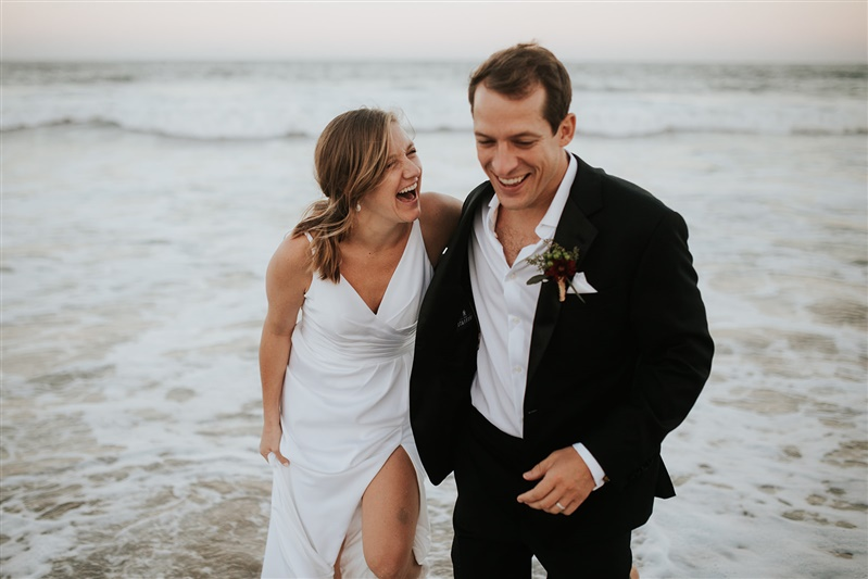 newlywed couple laughing and walking in the ocean along the beach after their wedding virginia Carly Romeo & Co