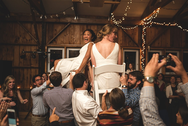 newlywed couple being lifted up in chairs by their wedding guests at reception in richmond virginia by carly romeo & Co