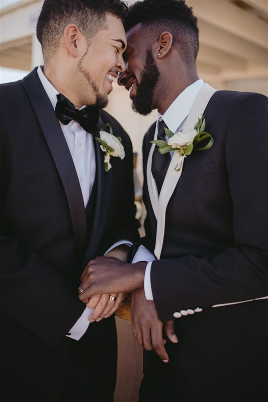 two grooms holding hands and leaning in for a kiss after their wedding Richmond Virginia Carly Romeo & Co