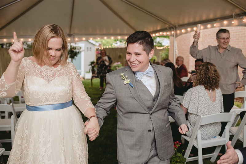 newlywed couple holding hands and dancing as they exit their wedding ceremony in richmond virginia Carly Romeo & Co