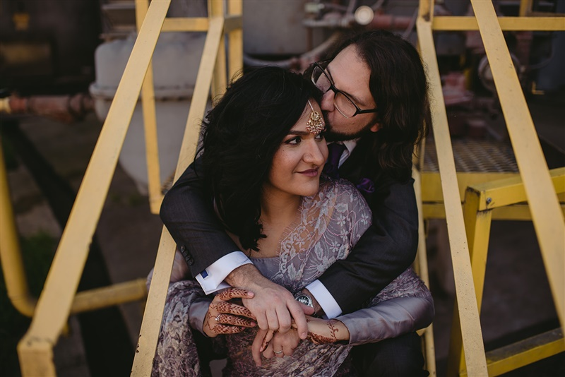 newlywed couple with bride in henna and traditional attire sitting on steps and being kissed on cheek by partner in richmond virginia Carly Romeo & Co