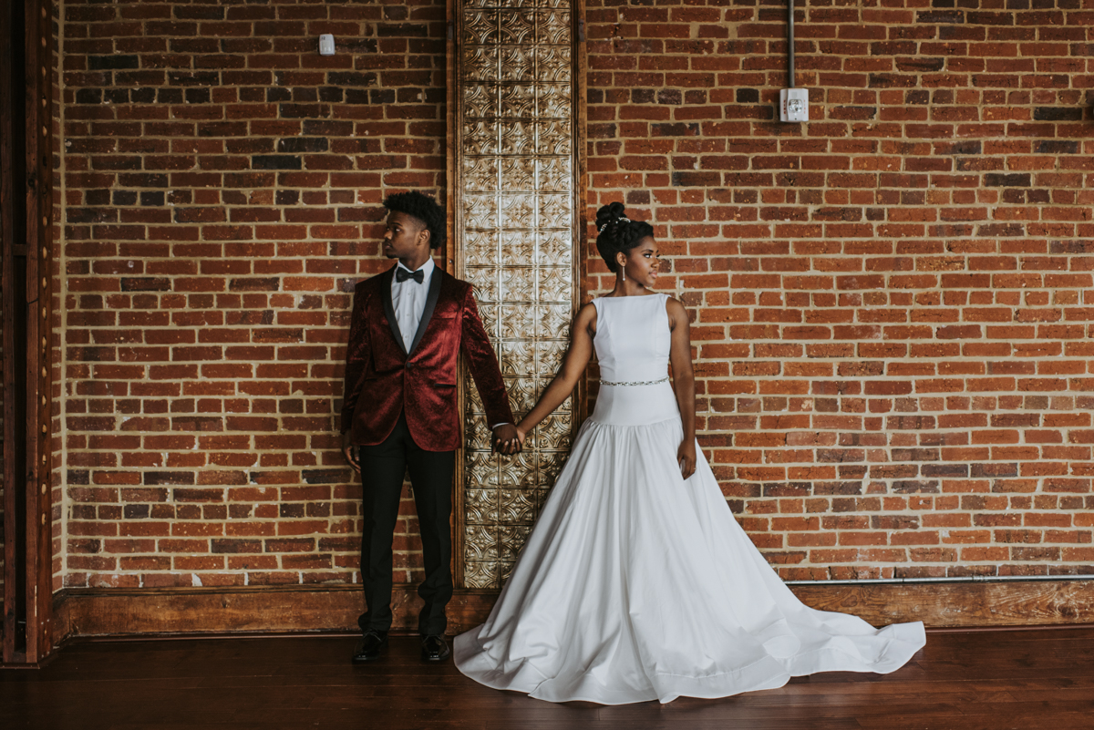 vintage vegan glam in Washington DC HFB Photography couple holding hands in front of brick wall, looking away from each other