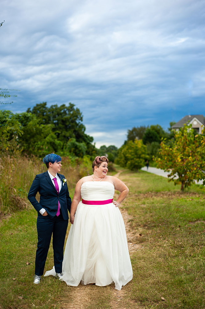 newlywed couple hold hands in field while looking off at their guests Atlanta Georgia You Are Raven Wedding Photography