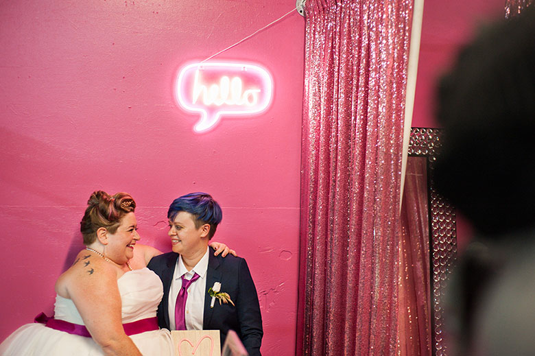 lgbtq couple smile at each other behind pink neon hello sign at wedding reception Atlanta Georgia You Are Raven Wedding Photography