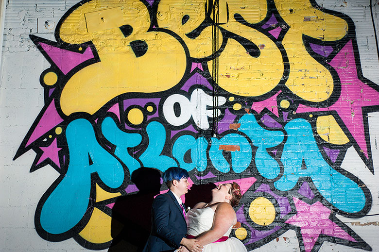 """newlywed couple laughs and bride leans head back in from of mural that reads """"Best of Atlanta"""" at wedding Atlanta Georgia You Are Raven Wedding Photography"""