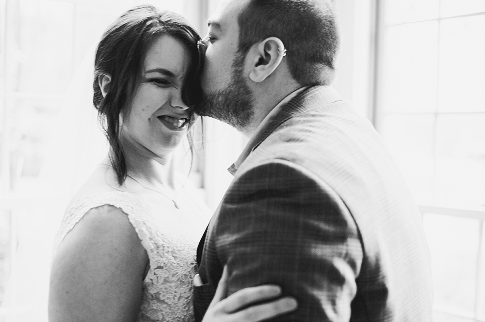 groom kisses bride on forehead during first look at their wedding Atlanta Georgia You Are Raven Wedding Photography