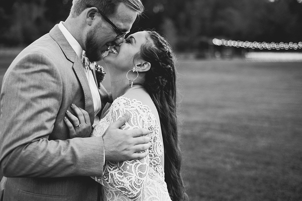 newlywed couple excitedly lean in for kiss in field after wedding Atlanta Georgia You Are Raven Wedding Photography