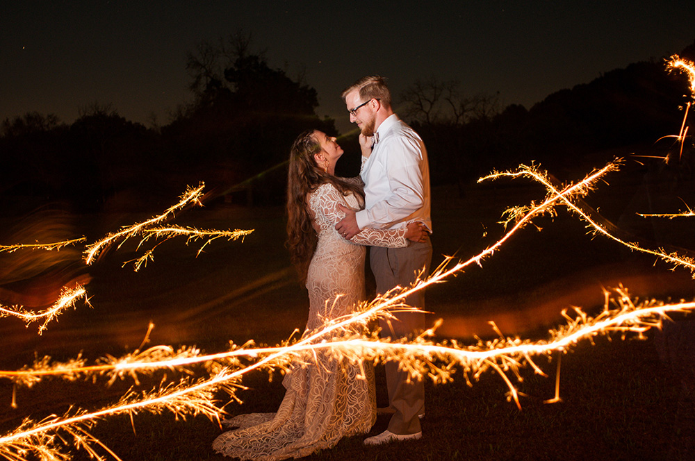 groom and bride in bold lace wedding dress stares into each other's eyes surrounded by sparkler light lines Atlanta Georgia You Are Raven Wedding Photography