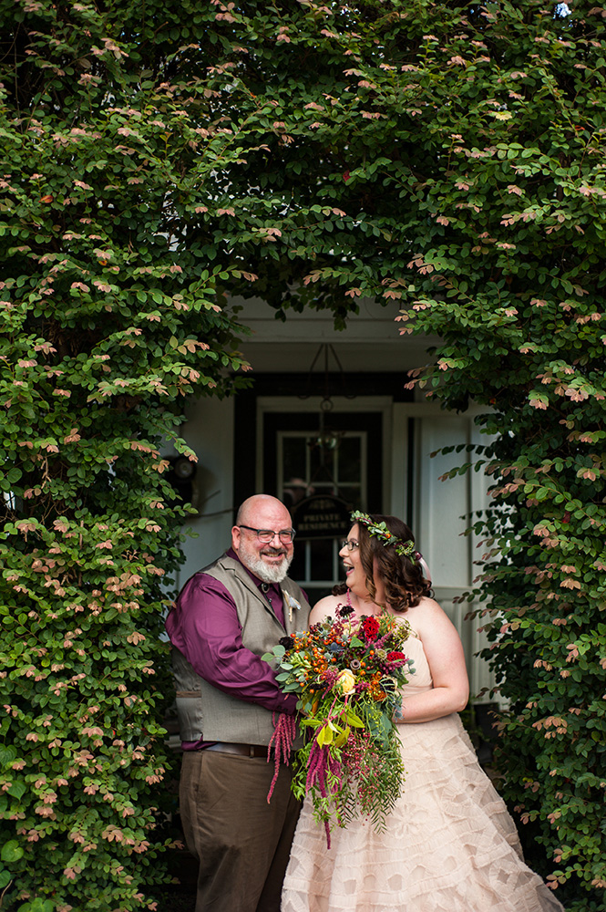 groom and bride in pink wedding dress laughing under green archway Atlanta Georgia You Are Raven Wedding Photography