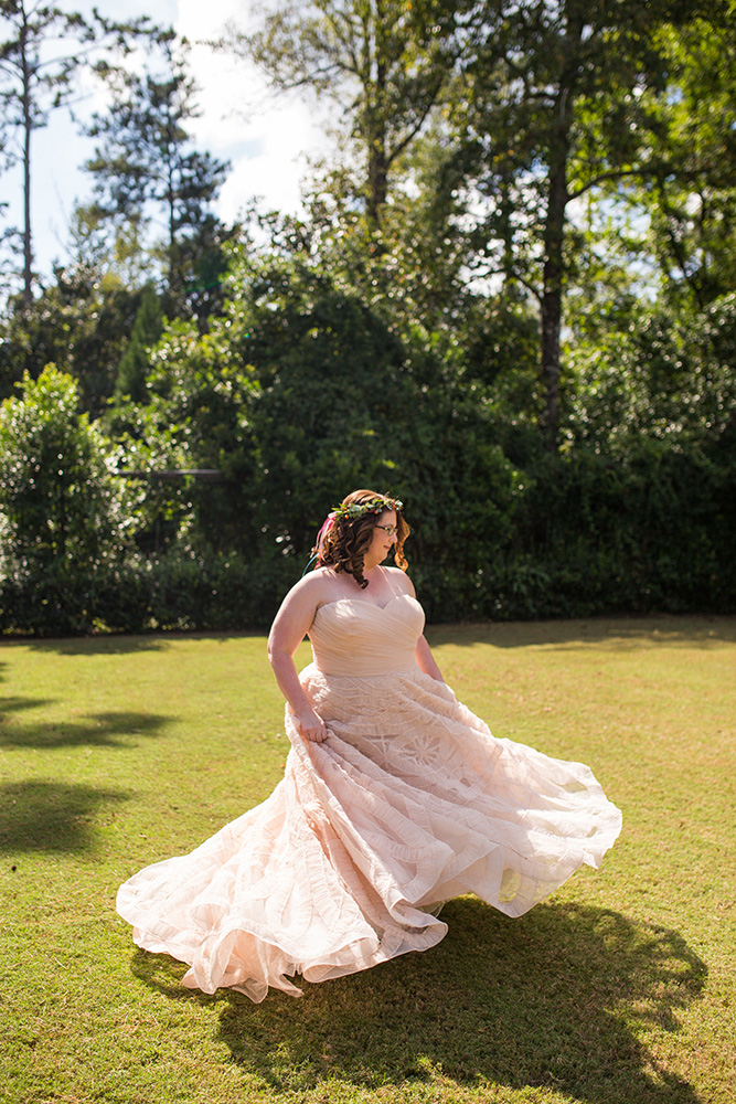bride in pink lace wedding dress and floral crown spins in a field Atlanta Georgia You Are Raven Wedding Photography