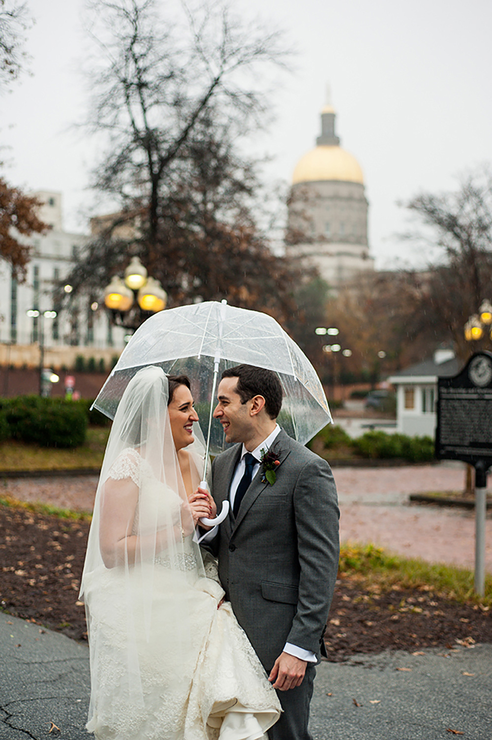 newlywed bride and groom huddle under clear umbrella after their wedding in Atlanta Georgia You Are Raven Wedding Photography