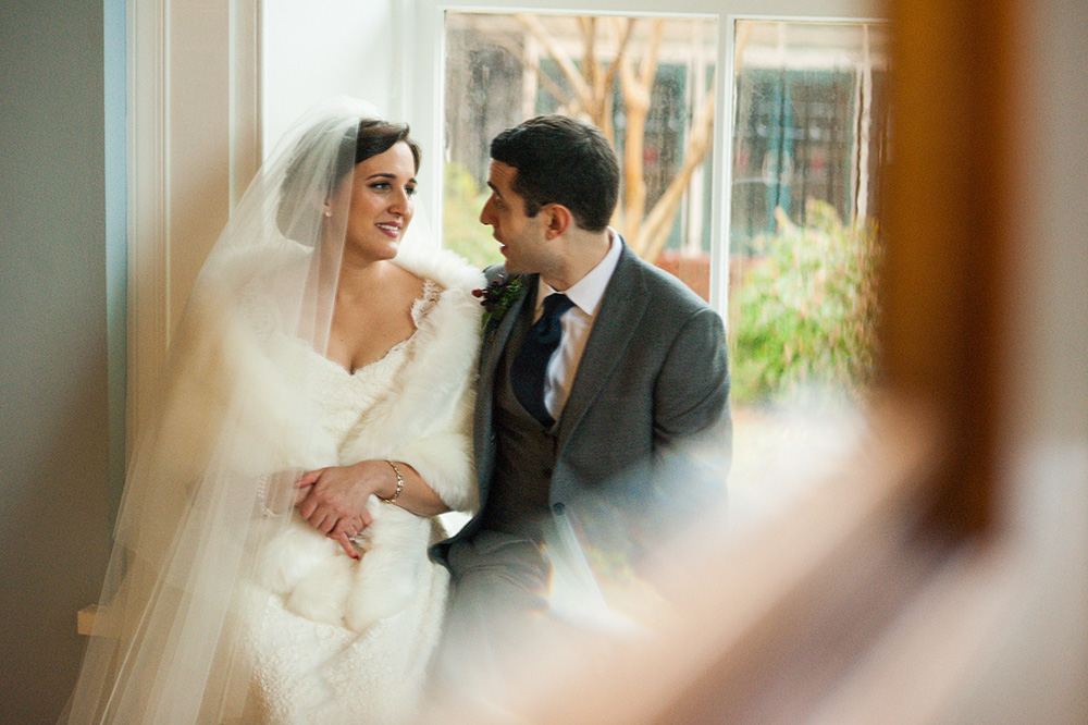 groom and bride in white fur and veil sit in window sill and stare at each other after their wedding Atlanta Georgia You Are Raven Wedding Photography