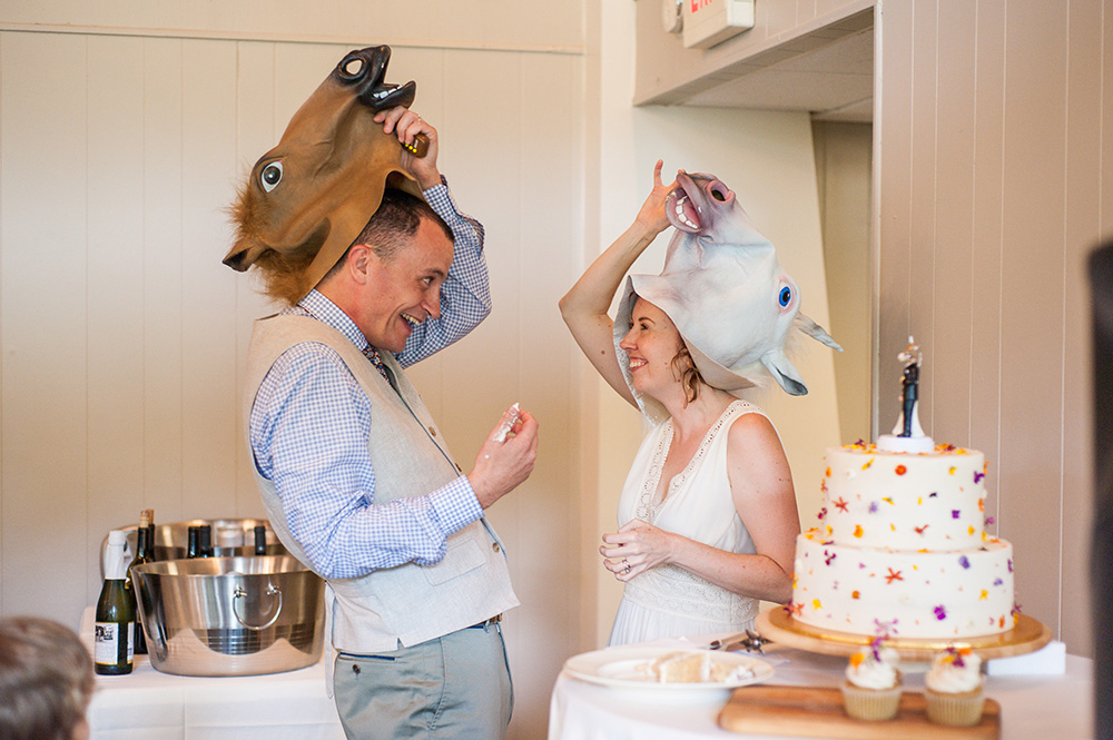 bride and groom wearing horse masks for cake cutting at wedding reception Atlanta Georgia You Are Raven Wedding Photography