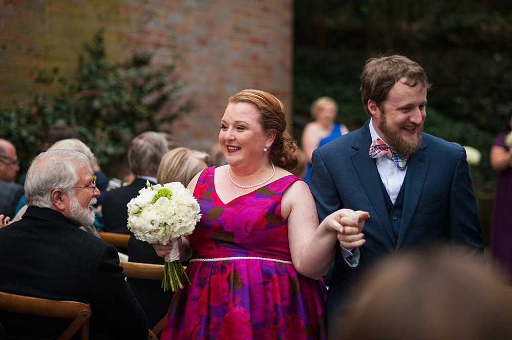 groom and bride in fuschia floral dress walk up aisle after their wedding Atlanta Georgia You Are Raven Wedding Photography