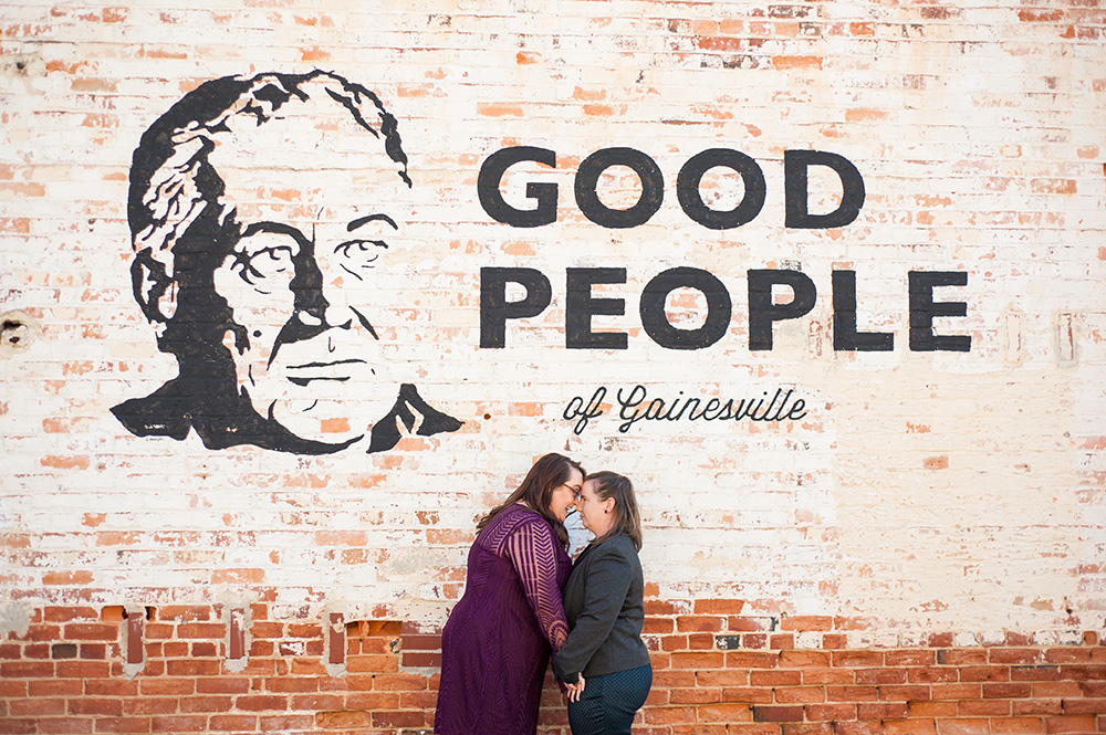"""lgbtq couple leans in for kiss in front of mural that reads """"good people of gainesville"""" for wedding engagement session Atlanta Georgia You Are Raven Wedding Photography"""