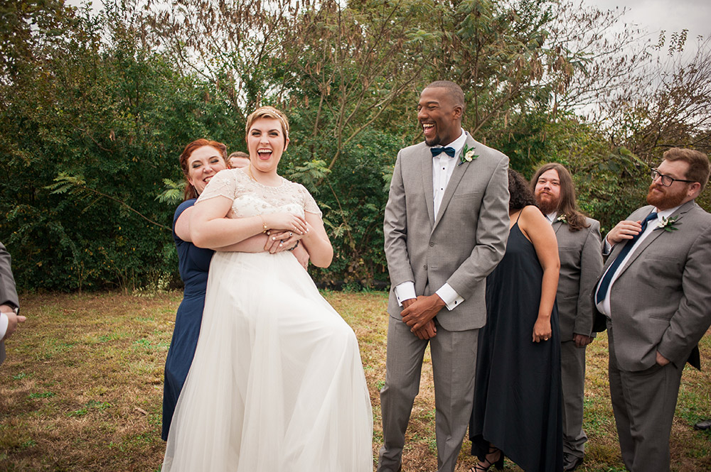 bride gets hugged from behind by bridesmaid during wedding ceremony Atlanta Georgia You Are Raven Wedding Photography