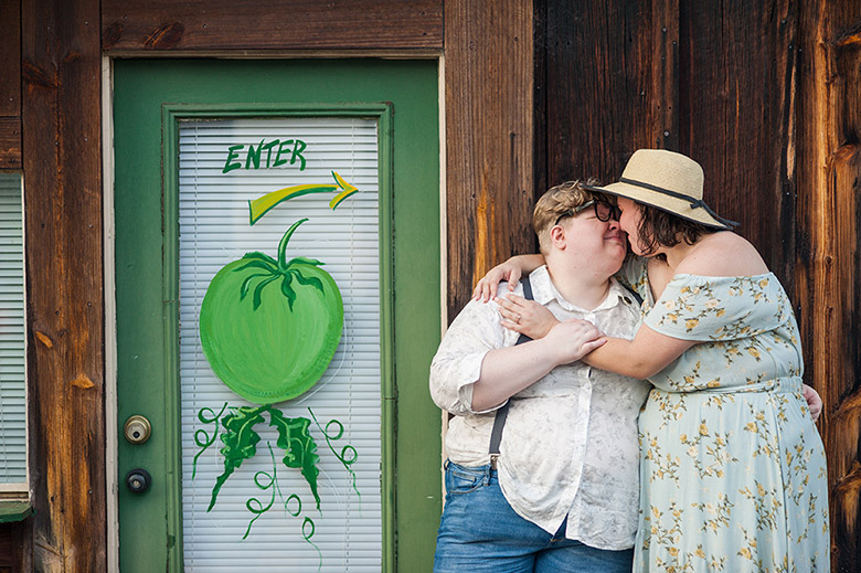 couple nuzzles noses in front of market at their summer wedding engagement Atlanta Georgia You Are Raven Wedding Photography