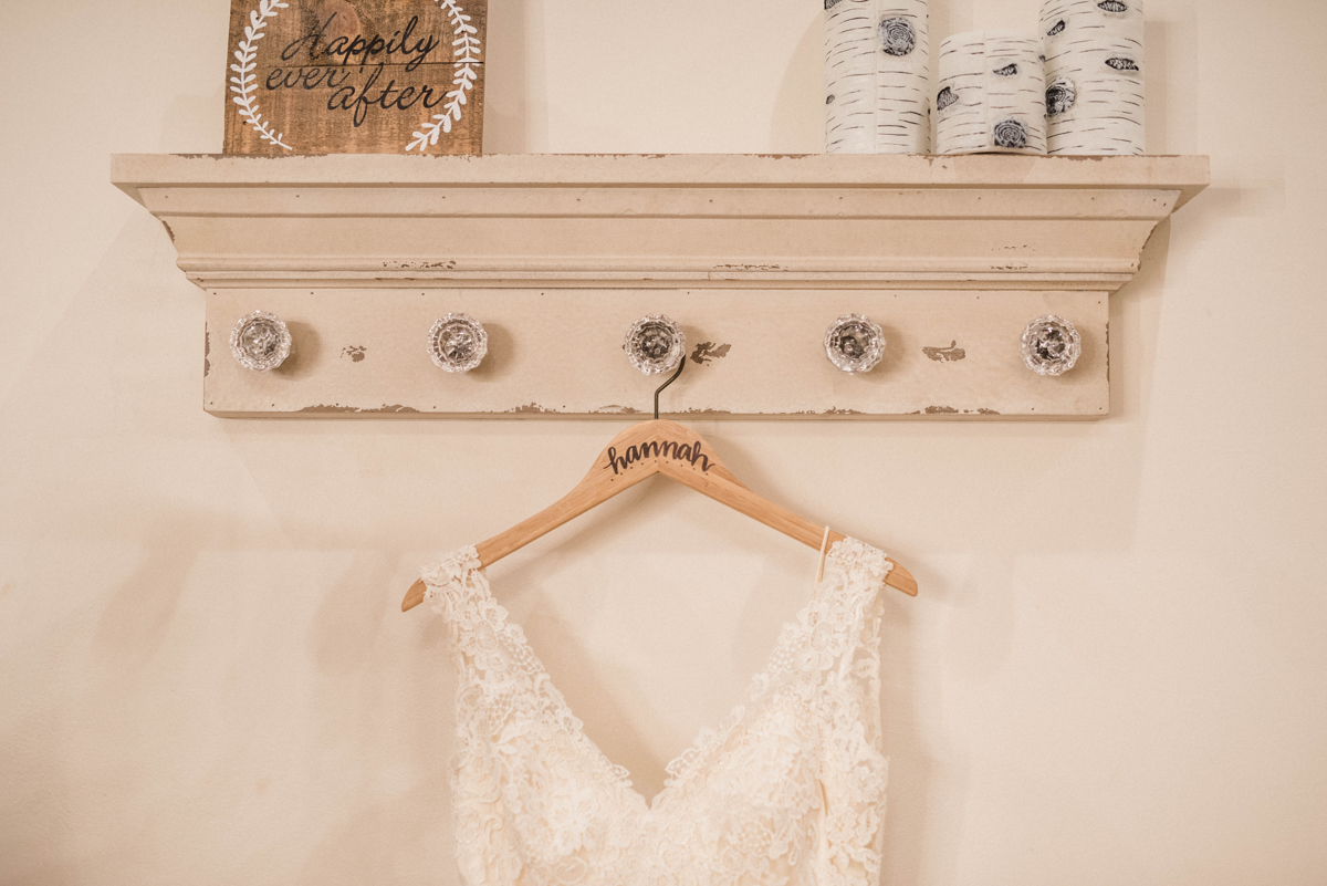 """PAVILION WEDING KANSAS CITY MISSOURI Hey Tay Photography hannah's dress hanging on shelf with wooden sign reading """"happily ever after"""""""
