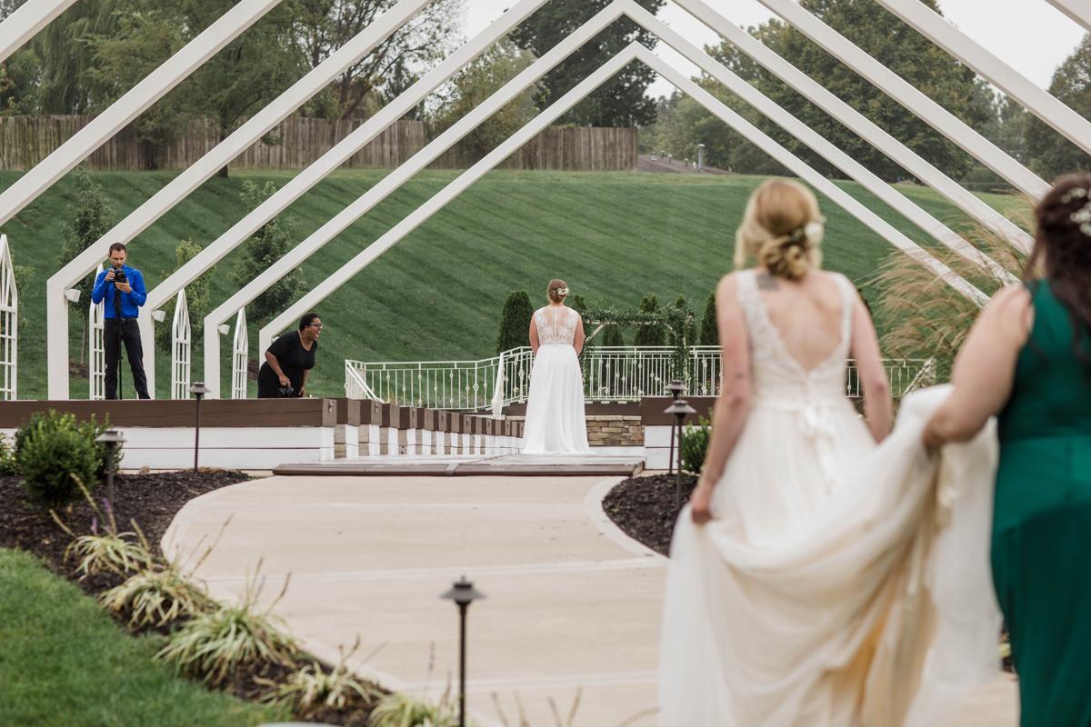 PAVILION WEDING KANSAS CITY MISSOURI Hey Tay Photography hannah walking down sidewalk to surprise meredith, both wearing wedding dresses