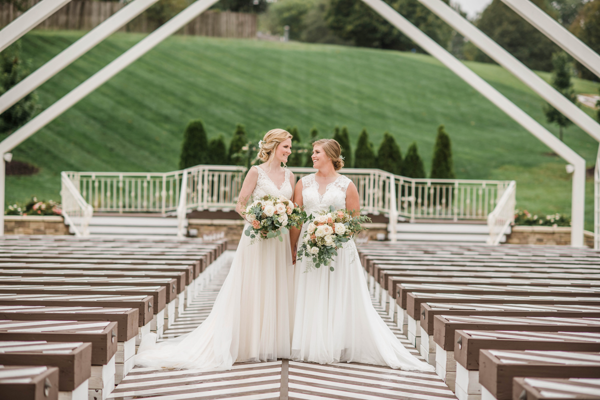PAVILION WEDING KANSAS CITY MISSOURI Hey Tay Photography hannah and meredith posing in middle of aisle with bouquets
