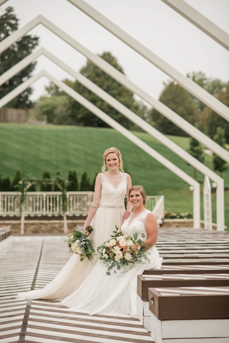 PAVILION WEDING KANSAS CITY MISSOURI Hey Tay Photography brides posing together, hannah standing and meredith sitting on bench