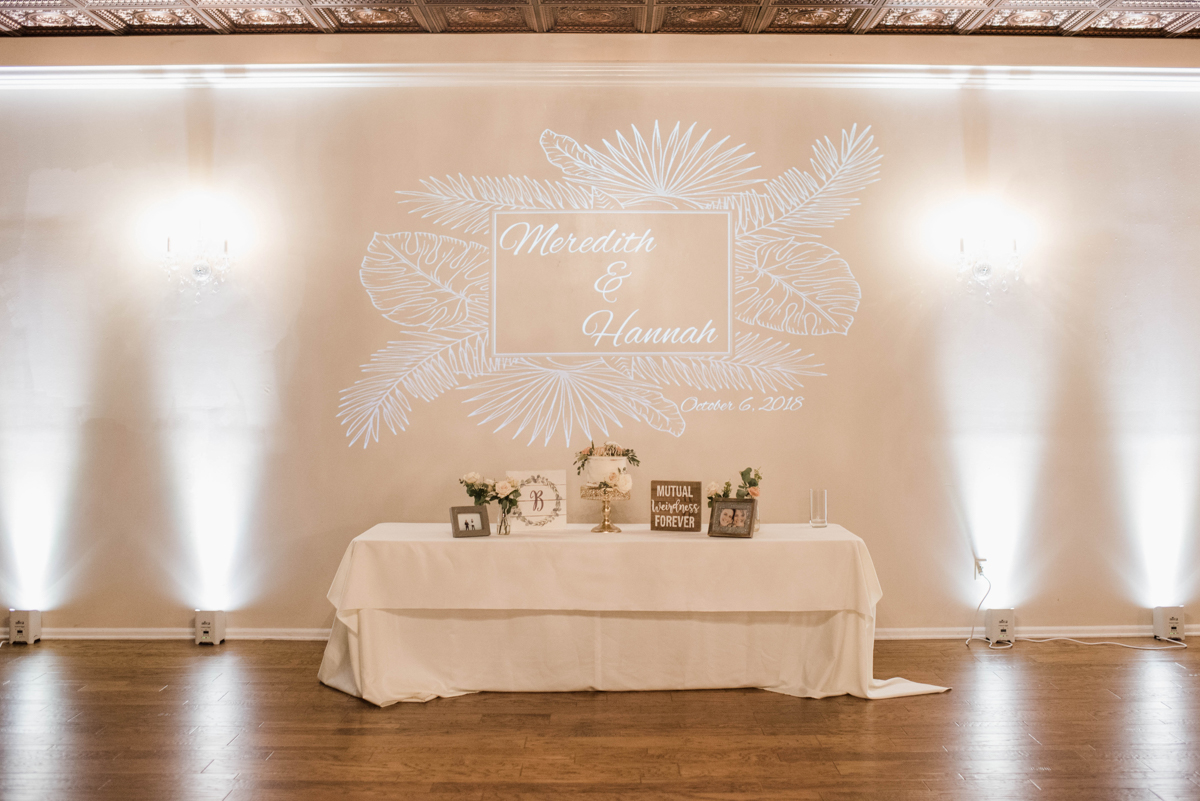 """PAVILION WEDING KANSAS CITY MISSOURI Hey Tay Photography table with cake and pictures, """"meredith & Hannah"""" projected on wall above"""