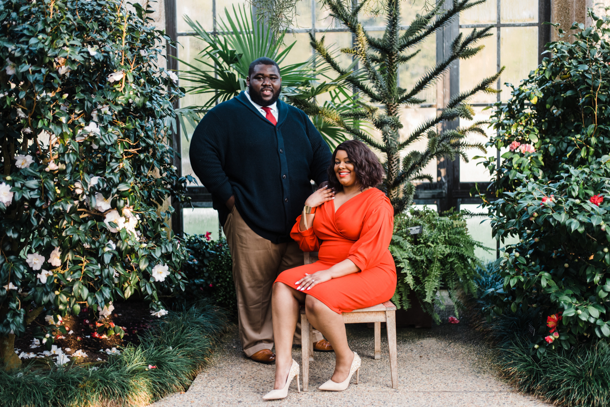 longwood gardens engagement kennett square pennsylvania sgw photography yasmine sitting in chair with angelo's hand on her shoulder